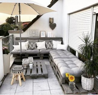 a rooftop garden with DIY pallet furniture, including a corner bench and coffee table