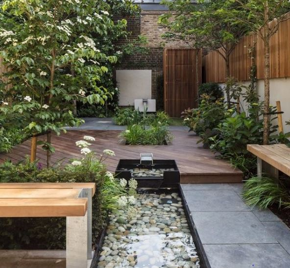 an urban garden with a raised deck and sunken water feature