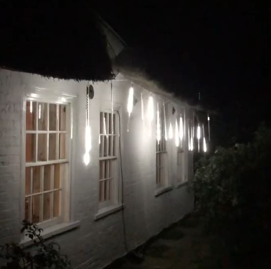 meteor lights hanging from the outside of a thatched cottage