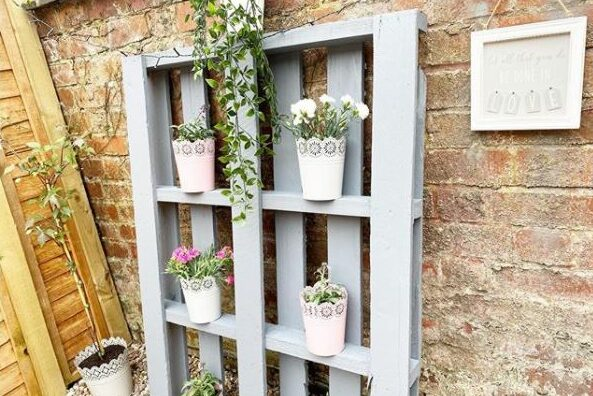 DIY garden pallet ideas using paint and leaning the pallet against the wall to use it as a shelf