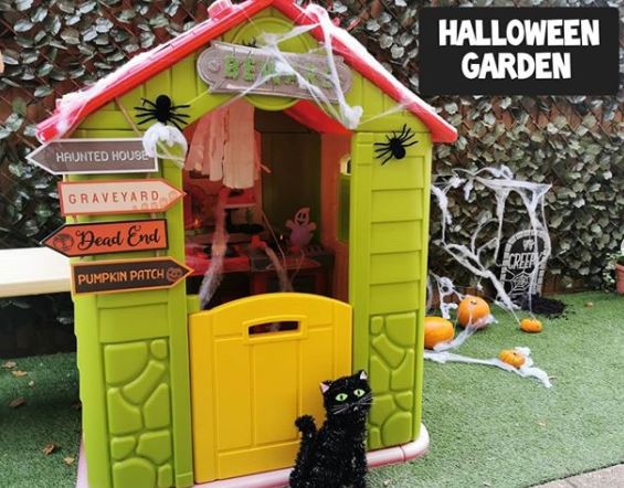 a toy playhouse decorated with fake cobwebs, spooky direction signs and a toy black cat