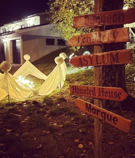 a wooden directions sign pointing to spooky locations, on a lawn with illuminated ghosts made from sheets