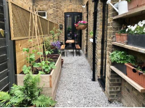 a narrow side-return garden with gravel, seating area, vegetable planter and flowers in pots on shelves