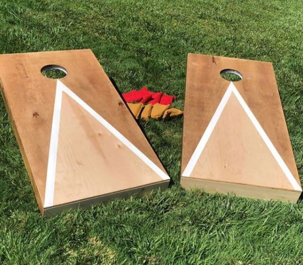 two DIY cornhole ramps on a lawn with beanbags to play the game