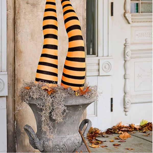 two mannequin legs in striped orange tights, standing upside-down in a planter