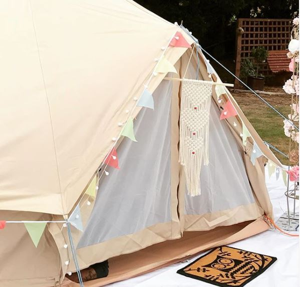 a canvas bell tent with pretty bunting lights and decor for garden camping