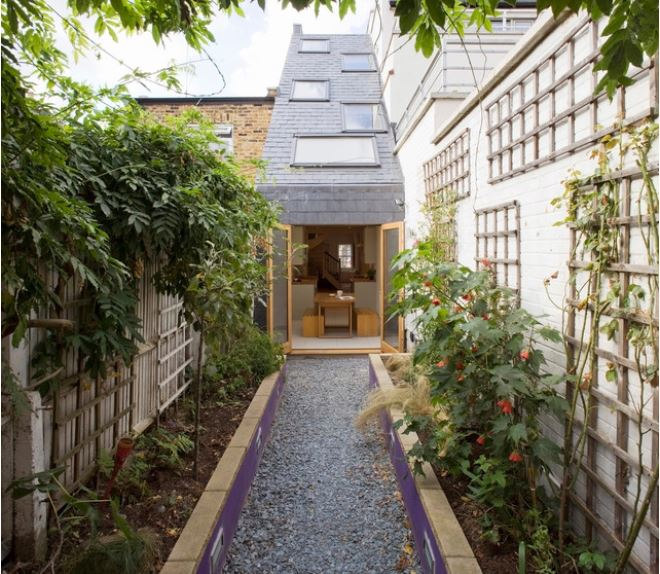 a very narrow garden with a gravel path and planters and trellises on either side