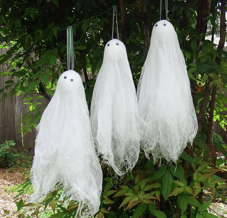 three ghosts made from lace and gauze, hanging from a branch as if they are floating