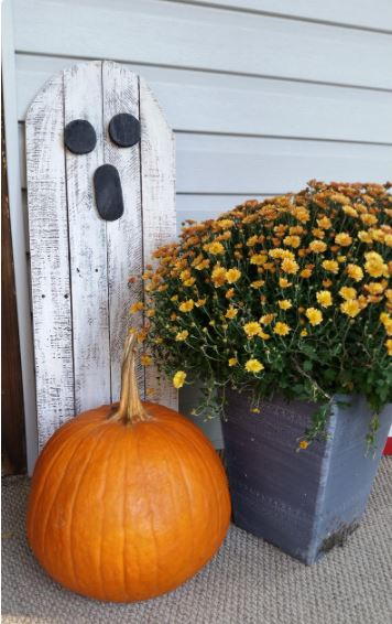halloween garden ideas using whitewashed wooden planks nailed together and painted with a ghostly face