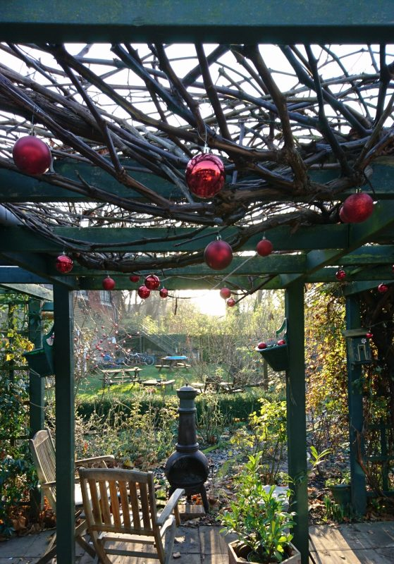 a pergola covered with wintery branches and festive red baubles