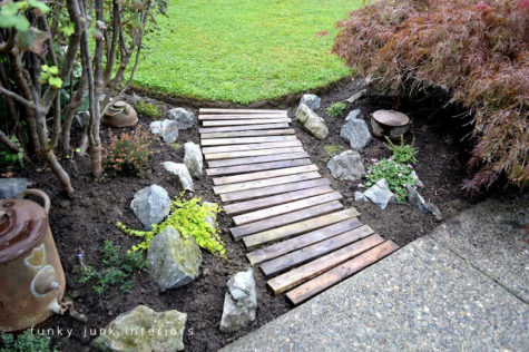 a wooden walkway made from parts of pallet