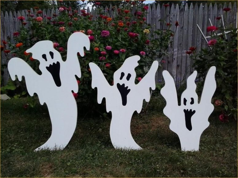 jolly looking ghost sculptures made from cut wood panels