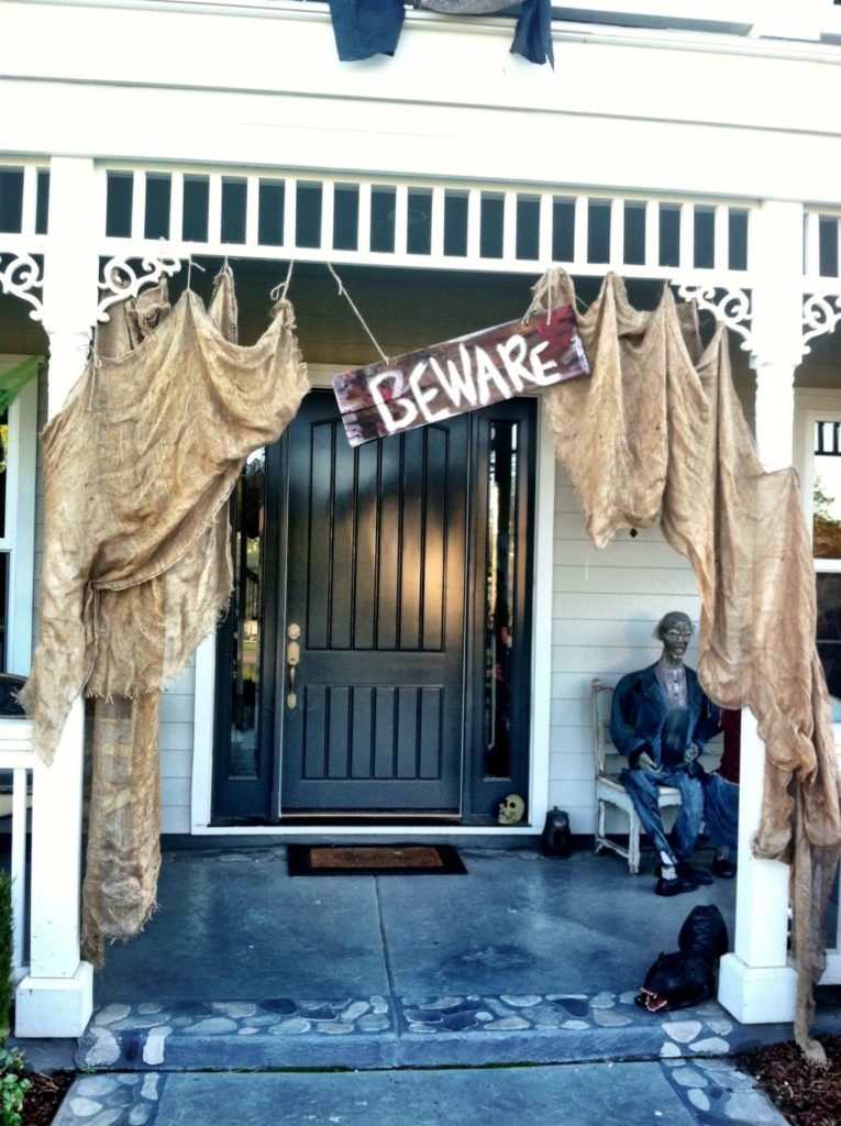 """a house porch decorated with stained sacks and a sign that says """"beware"""""""
