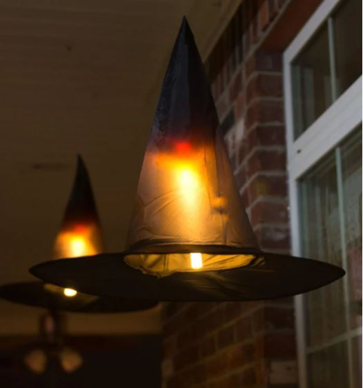 black pointed hats with a light inside, hanging on a porch