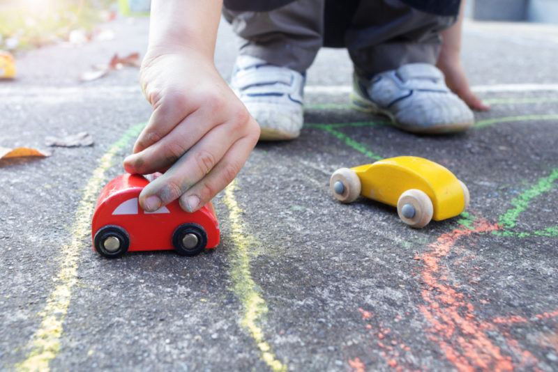 child playing with wooden toy cars along a track drawn in chalk on concrete