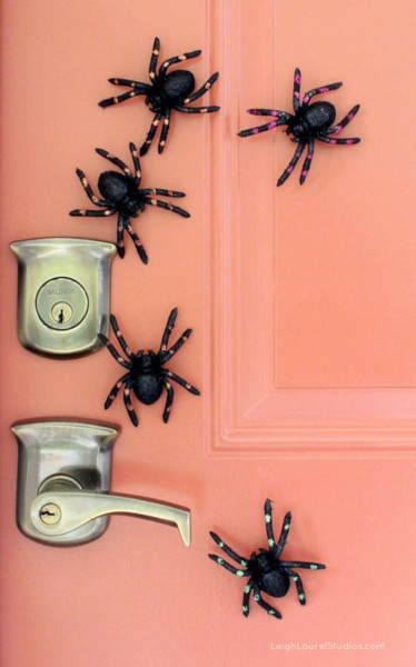 magnetic toy spiders clustered around the handle on a metal door