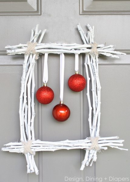 a square wreath framing three red baubles