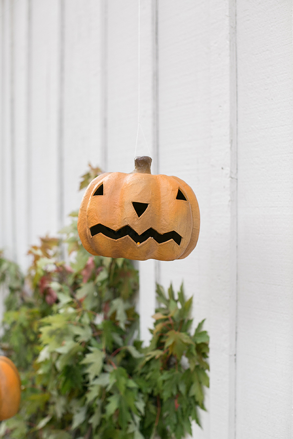 a paper mache pumpkin hung up with fishing wire to look like it is floating