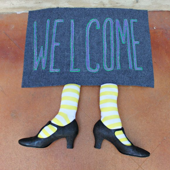 two stuffed socks and pointy shoes poking out from beneath a welcome door mat