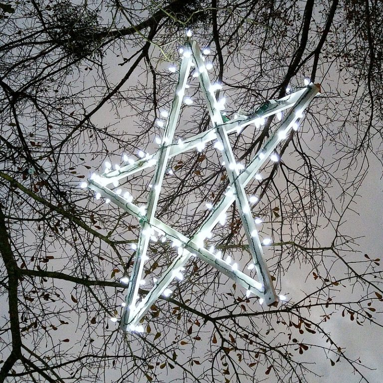 a large wooden star covered in string lights hangs in a tree