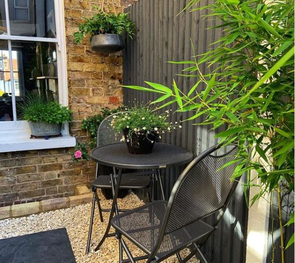 a snug seating area with black bistro table and chairs