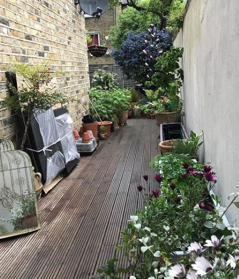 side return garden ideas with a solid deck walkway and potted plants