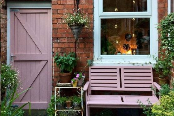 the wall of a house with a wooden bench painted pink and a side gate painted in the same colour