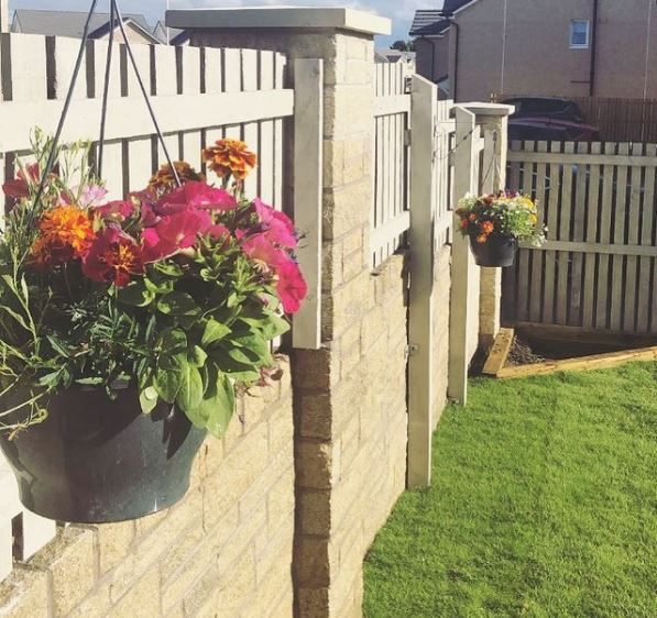 a fence with hanging baskets filled with pink and orange flowers