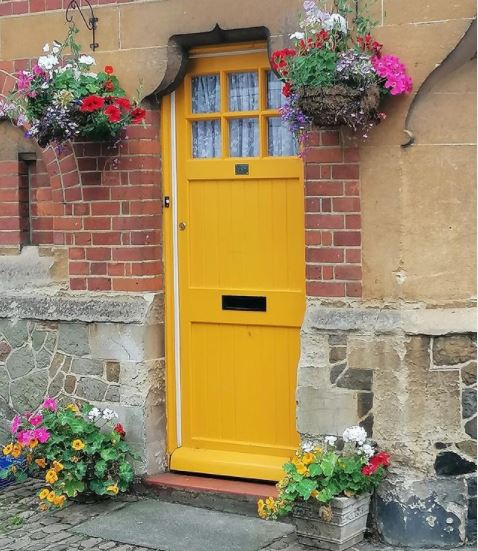 a cheerful yellow door with hot pink flowers in hanging baskets either side
