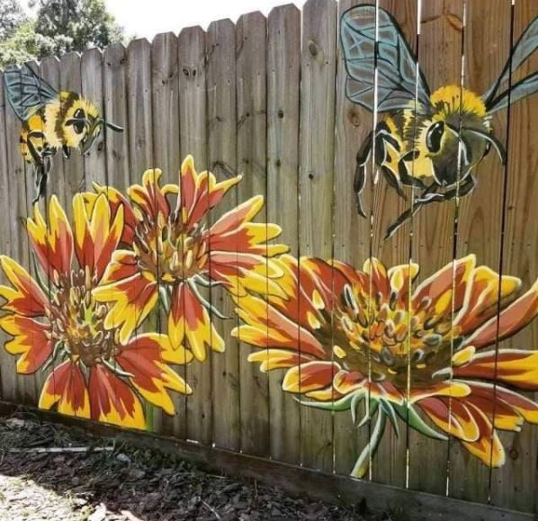 a fence with a bright mural of bees and flowers