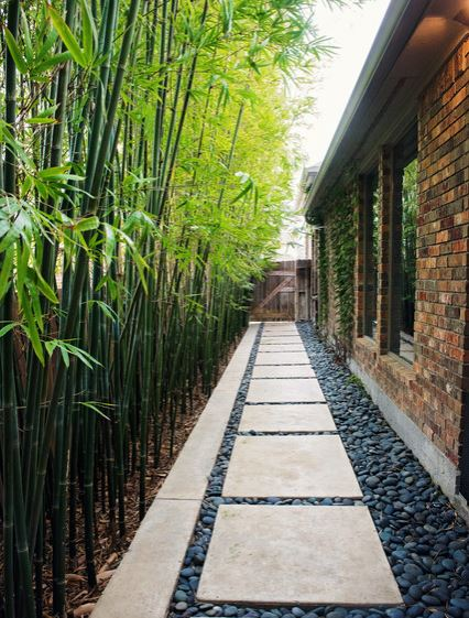 japanese inspired side return garden ideas, with natural stone slabs, dark gravel and bamboo along the fence