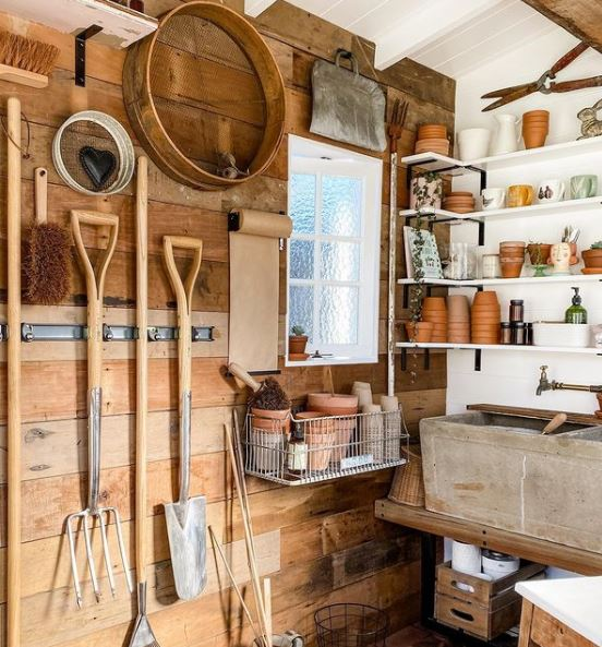 an organised shed with wall mounted tools and tidy shelves with pots