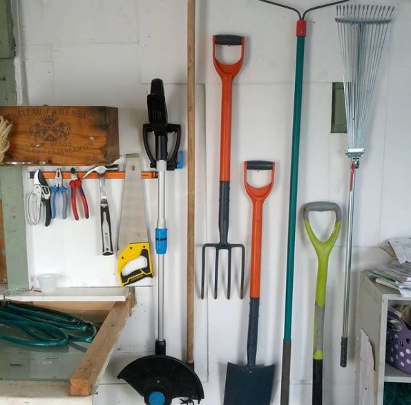 a shed wall with various garden tools hanging on hooks