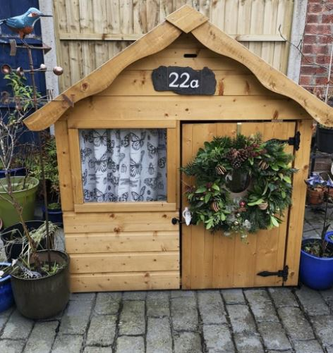 a wooden playhouse with a large festive wreath on the door and a slate house number