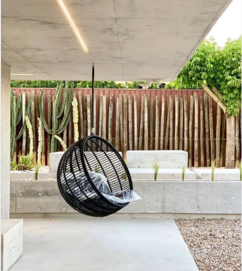a black wicker garden swing chair hanging from a concrete roof, above a concrete floor, with a wooden fence and spiky green plants in the background