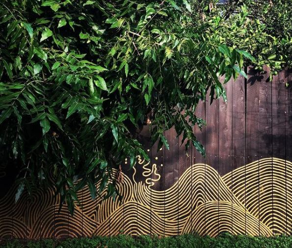 a brown fence partially covered by a hedge, with a line painting of ocean waves at the bottom