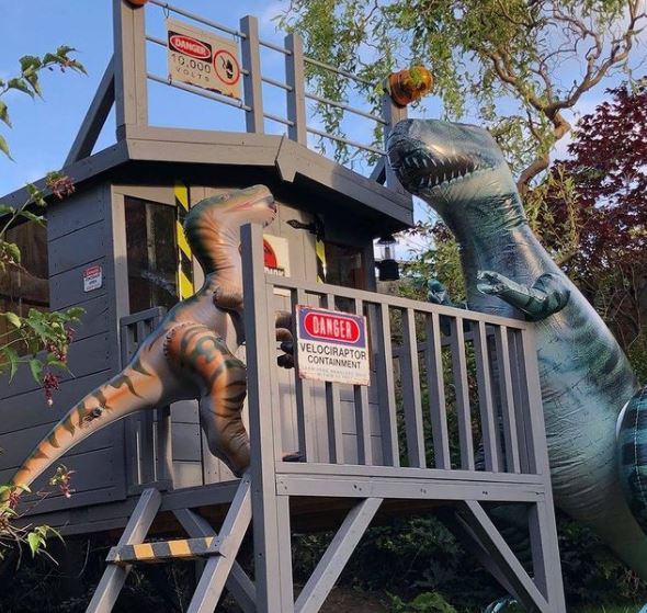 a playhouse on a platform, decorated with fencing and keep out signs to resemble a security cabin. Two inflatable dinosaurs block the entrance