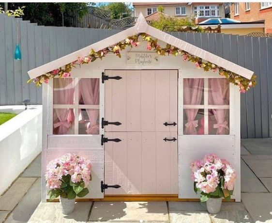 a pretty playhouse with pink curtains, a pink door and pink flowers outside