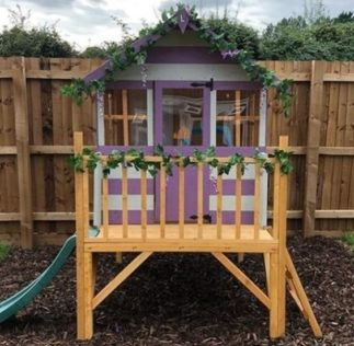 a playhouse painted with purple and cream stripes, on a raised platform with steps and a slide