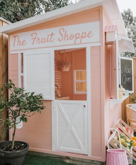 """a peach coloured shed with a hand-painted sign that reads """"the fruit shoppe"""" with a counter and pretend goods for sale"""