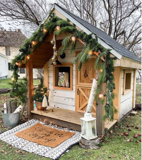 scandinavian-inspired garden playhouse ideas with wreaths of foliage, string lights, hygge style door mat and rustic decorations