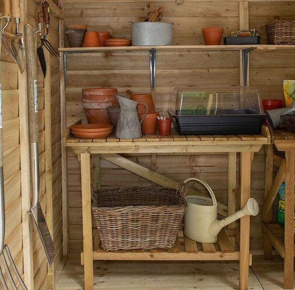garden tool storage ideas using a wooden work bench with storage underneath, in a tidy shed