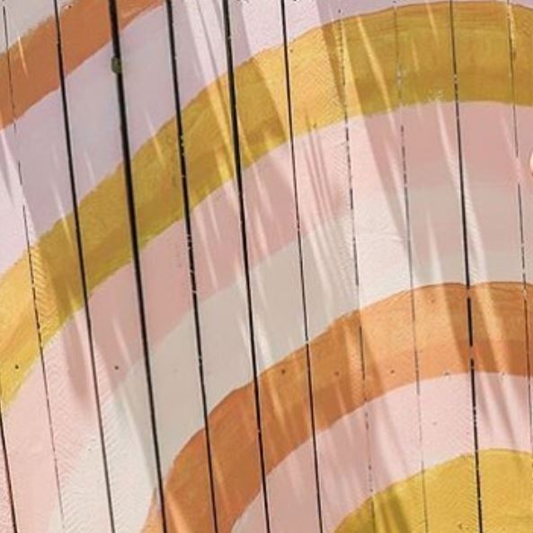 fence panels painted with bands of orange, gold, cream and peach