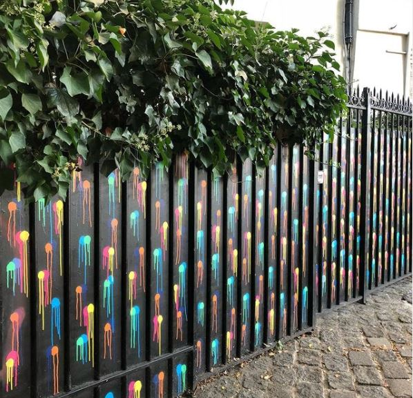 a black fence with sprayed-on paint circles of blue, red, turquoise and yellow