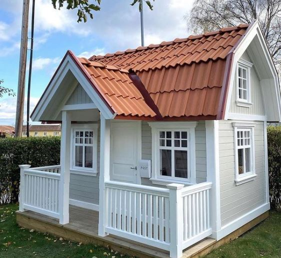 a playhouse styled to look like an american home with a red tiled roof