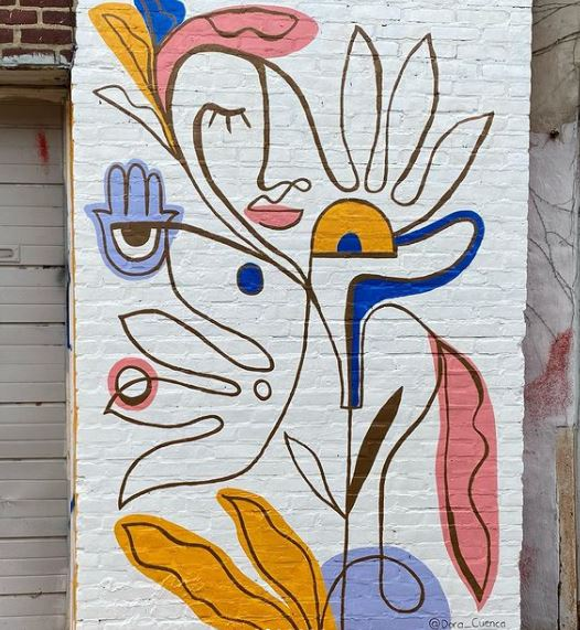 a creative line drawing with abstract depictions on a white brick wall