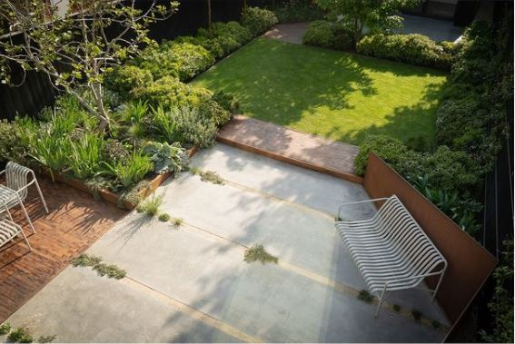 a garden with a contemporary deck and concrete patio, leading to a lawn