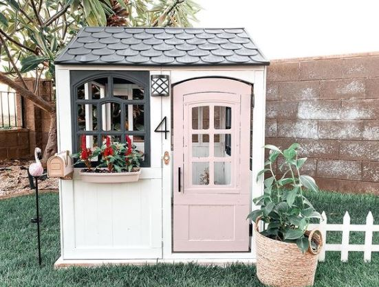 a grown-up playhouse for kids with a pastel pink door, picket fence and window box with flowers