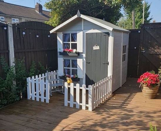 a garden shed turned into a playhouse with a sun deck marked out with a picket fence