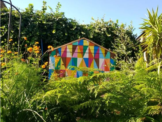 a garden shed painted with brightly coloured triangles